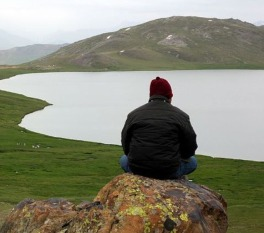 traveling solo- Person sitting on a rock overlooking a lake